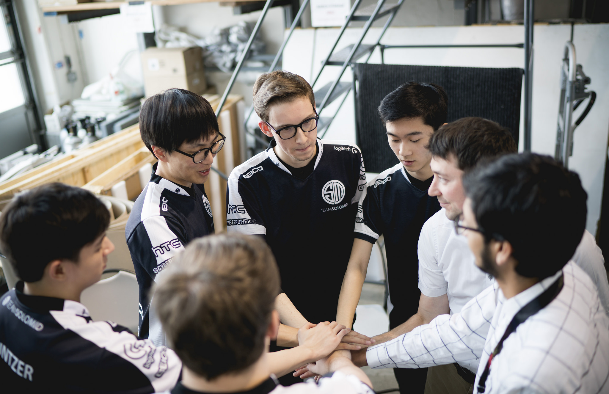 A photo of Team SoloMid (TSM) standing in a circle and putting their hands together in the middle.